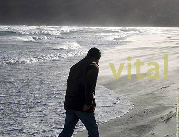 Male figure with head covered walking along beach close to stormy waves and spray, Allans beach Otago peninsula