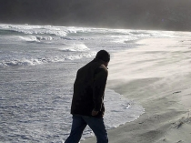 Male_figure_with_head_covered_walking_along_beach_close_to_stormy_waves_and_spray,_Allans_beach_Otago_peninsula